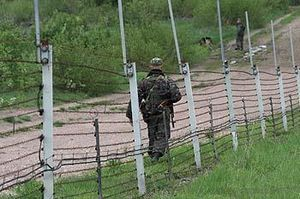 A solider in camouflage walks next to a gravel road inside a wire fence with white posts.