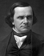 Photograph of a man with longish dark hair; he is wearing formal attire which consists of a dark vest, a white shirt, and a tie of the style worn in 1860.