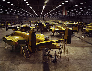 Interior of huge aircraft factory where rows of bombers are being assembled.