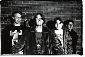 Pavement members standing before a brick wall posing in a black-and-white photo