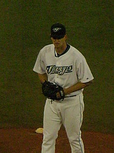 "A man in a white baseball uniform reading ""Jays"" across the chest, dark baseball cap, and black baseball glove stands on a dirt mound in a grass field."