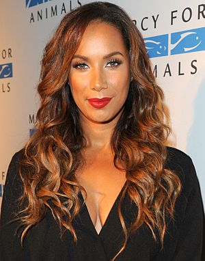 A woman with long, curly brown hair wearing looking directly forward, wearing a black outfit, and red lipstick.