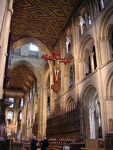 This interior view of Peterborough shows part of the very long nave and the chancel with no screen dividing the building. The structure is mostly of a unified Norman appearance with three levels of simple round-topped arches, only the tall arches of the central tower being Gothic. Other visible features are the ancient painted ceiling, the medieval choir stalls and the modern Rood, which has a gilt wooden figure of Christ on a red cross suspended high in front of the tower arch.