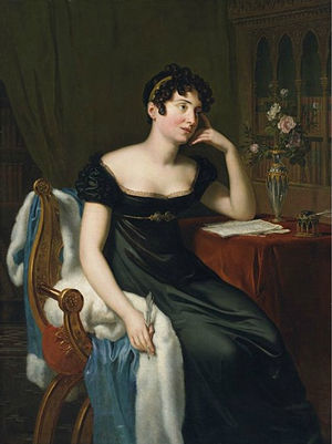 Full-length painted portrait of a woman sitting at a table, writing, and leaning on her hand. There are roses on the table, which is covered with a red, velvet cloth. She is wearing a dark green dress, which reveals her bosom. She has short, brown curls.