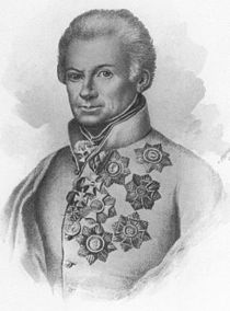 Black and white print of a man whose hair is combed back and who appears to have an injury to his right eye. He wears a white military uniform with numerous awards pinned to the left breast.