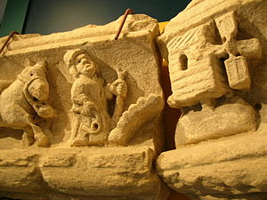 A photograph of a sandstone carving, broken into two pieces; on the left is the front half of a donkey, in the middle a fat man with a stick and a whip whilst on the right is a stylised windmill.