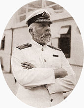 Photograph of a bearded man wearing a white captain's uniform, standing on a ship with his arms crossed