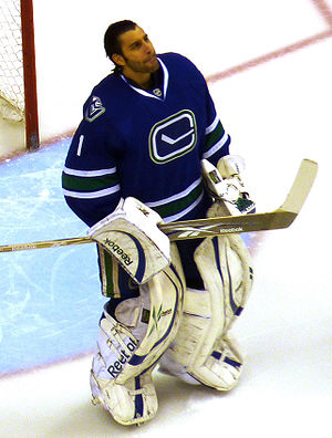 An unmasked ice hockey goaltender. His hair is slicked back and he is looking upwards. He wears white goaltending pads and a blue jersey with a logo of a stylized hockey stick.
