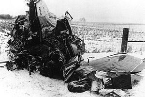 A tangled mass of metal with a wing and landing gear wheel barely recognizable, on a snowy field