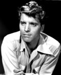 Burt Lancaster in 1947s Desert Fury—a handsome white man with light eyes and wavy light-colored hair, oval face, wearing a light-colored shirt, around 34 years of age.