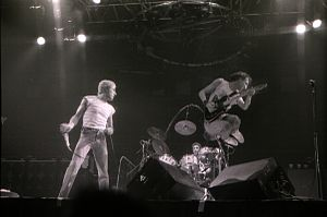 Roger Daltrey holding a microphone and Pete Townshend jumping on stage