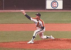 A man in a white baseball uniform with orange and red stripes across the chest throws a baseball with his right hand from a dirt mound on a grass field.