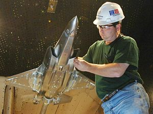 Engineer handling a metallic scale model of jet fighter in wind-tunnel