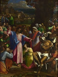 Realistic painting of a robed figure, arms extended, standing outside on a small platform among people doing various things such as talking to each other, but most of whom are looking at him.