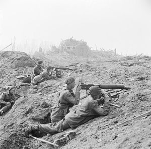 A black and white photograph of a battle scene in which two Vickers machine guns are firing from behind cover of a pile of rubble. Each machine gun is crewed by two men, a firer and an observer with a pair of binoculars. Another soldier is looking on from behind the crews