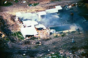 An aerial view from a helicopter of the Mount Carmel Center building. Large columns of smoke are arising from the left side of the building from a fire. One side of the building shows extensive damage. The building is surrounded by dirt paths.