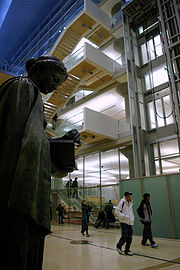 Patrons walking towards door in modern lobby with 19th C.  bronze sculpture of Minerva by Jakob Fjelde on left