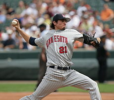 "A man in a pinstriped gray baseball uniform throws a pitch with his right hand. His uniform reads ""Minnesota"" in red letters, and he wears a black baseball glove on his left hand."
