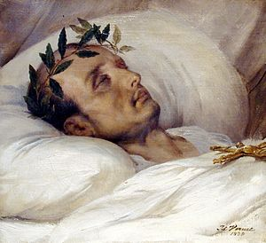 Gold-framed portrait painting of a gaunt middle-aged man with receding hair and laurel wreath, lying eyes-closed on white pillow with a white blanket covering to his neck and a gold Jesus cross resting on his chest