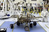A robotic rover rests on a blue floor, while several scientists wearing white bodysuits observe it.