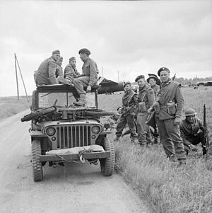 A black and white photograph of a jeep with soldiers sitting on top and standing beside it. The soldiers sitting on the jeep are three German soldiers and one British soldier who is interrogating the Germans. On the bonnet of the jeep is small motorcycle, while in the background is a Horsa glider