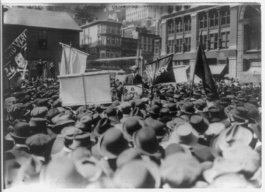 A large crowd of people, some carrying banners. A man in the center is elevated above them and speaking to them