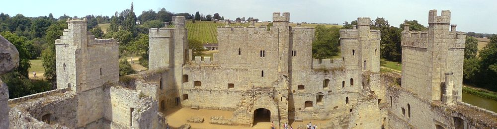 The courtyard of Bodiam Castle with the ruins of domestic buildings. In the centre of the image is the three-storey gatehouse. The curtain wall and the towers spaced along it are in good condition, contrasting with the interior. In the background, the landscape rises above the castle.