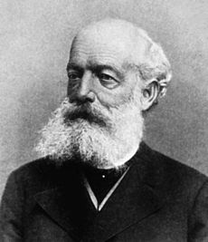 A black and white image of a bald man in a dark outfit, with a bushy white beard and moustache
