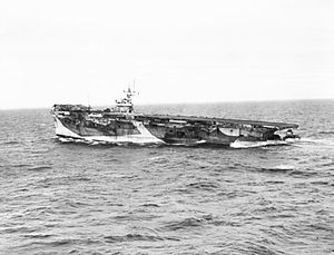 Black and white photograph of an aircraft carrier at sea. The stern of the ship is much lower in the water than the bow.