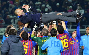 A group of association football players, who played for FC Barcelona at the time of the photo, lifting their coach after winning their second FIFA Club World Cup.