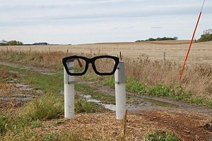 A sculpture of sort, consisting of two white posts holding a black spectacles frame in Buddy Holly's characteristic style
