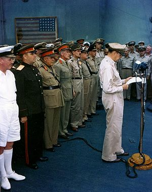 A man in a khaki uniform stands a microphone, reading from papers in his hand. A line of men in smart uniforms stands at attention behind him.