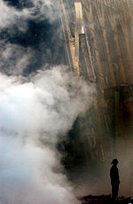 The very small silhouette of a firefighter with smoke in foreground and part of a collapsed building behind him