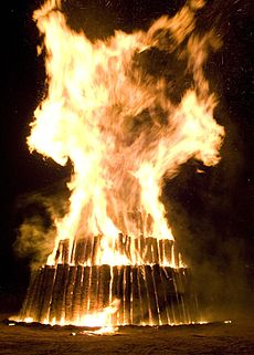 Large flames engulf the top layer of a circular three-tier structure of logs; the logs are vertical to the ground.